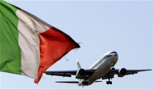 An Alitalia plane approaches to land as an Italian flag is seen at Fiumicino international airport in Rome
